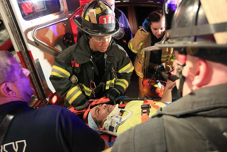 Fireman remove an injured man from the site of a crane collapse where construction is going on for the 7 line subway extension Tuesday, April 3, 2012, in New York. Fire officials say a crane collapse at a Manhattan construction site has injured two people.   (AP Photo/Frank Franklin II) Photo: Frank Franklin II, Associated Press