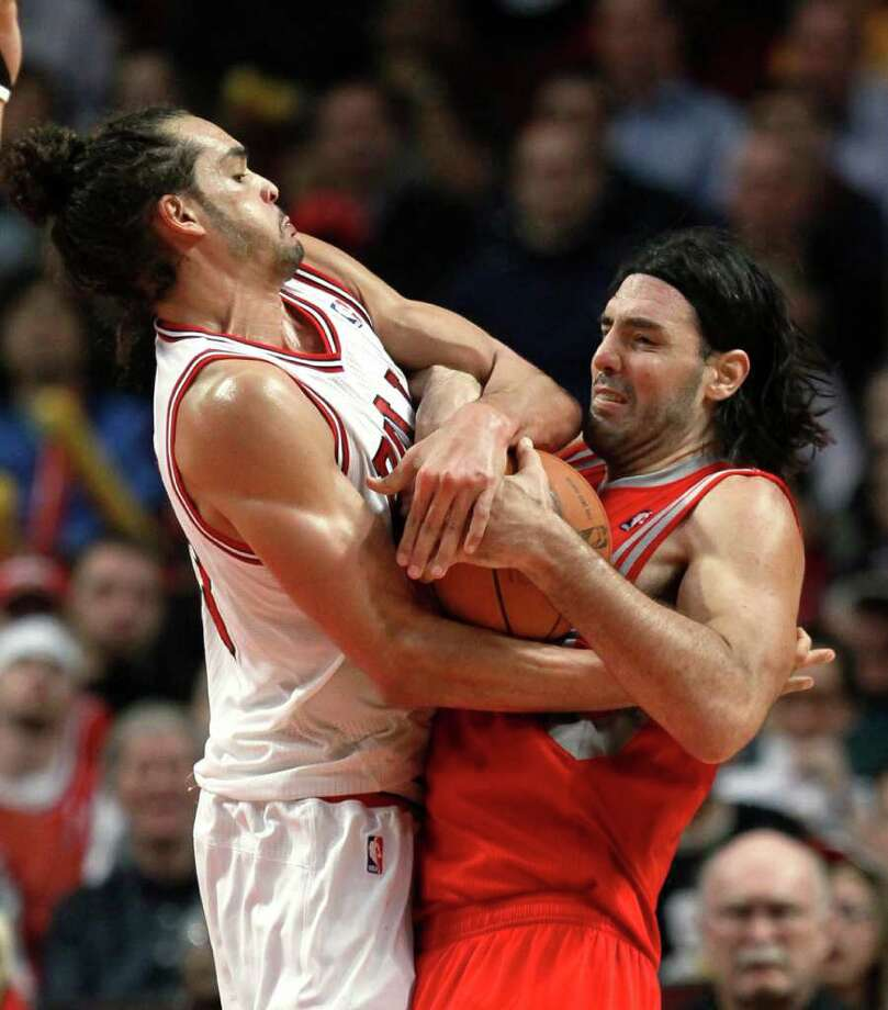 Chicago Bulls center Joakim Noah, left, ties up Houston Rockets forward Luis Scola, resulting in a jump ball, during the second half of an NBA basketball game Monday, April 2, 2012, in Chicago. The Rockets won 99-93. (AP Photo/Charles Rex Arbogast) Photo: Charles Rex Arbogast / AP