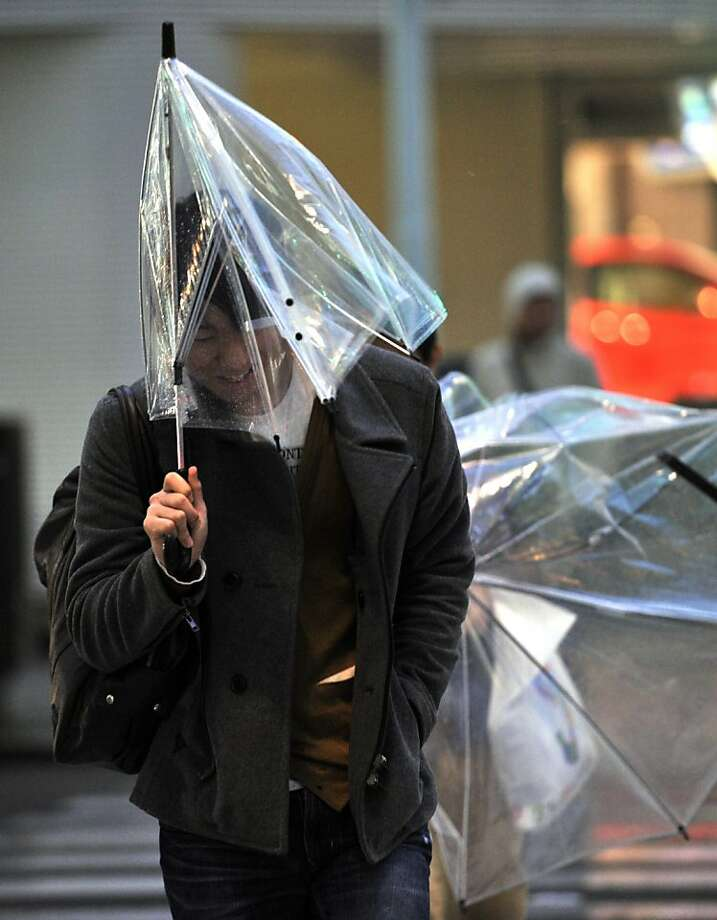 Pedestrians struggle amid strong wind in Tokyo on April 3, 2012. A typhoon-like spring storm brought strong gusts and heavy rains to Japan, causing traffic chaos, with meteorologists urging the public to stay indoors if possible. Photo: Yoshikazu Tsuno, AFP/Getty Images