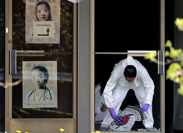 A crime scene investigator lifts the school's logo which was on the glass front door into the University,  as they continued to gather evidence on Tuesday April 3, 2012, in  Oakland, Ca., at the scene of yesterday's shooting at Oikos University where seven people were killed. Photo: Michael Macor, The Chronicle