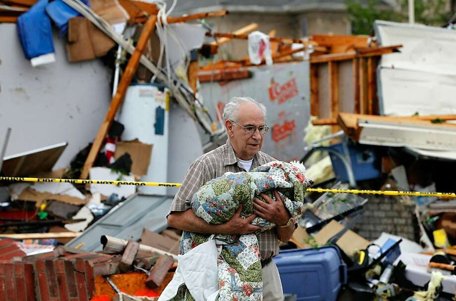 David Lowe carries his daughter's dog, Phoebe, after the dog was rescued from the rubble of a destroyed home on April 3, 2012 in Arlington, Texas. Multiple tornadoes touched down across the Dallas/Fort Worth area causing extensive damage. Photo: Tom Pennington, Getty Images