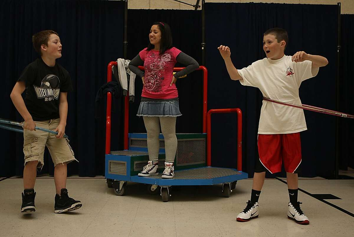 James Parker (left), 10 years old, and Riley Cronin (right), 11 years old, both in fifth grade, using the hula hoop before a performance from Kaiser Permanente for students at Monte Vista elementary in Rohnert Park, Calif., teaching them how to make healthy choices on Tuesday, April 3, 2012. Performance educator Natalie Amaya (middle) watching them as students get seated for the performance.