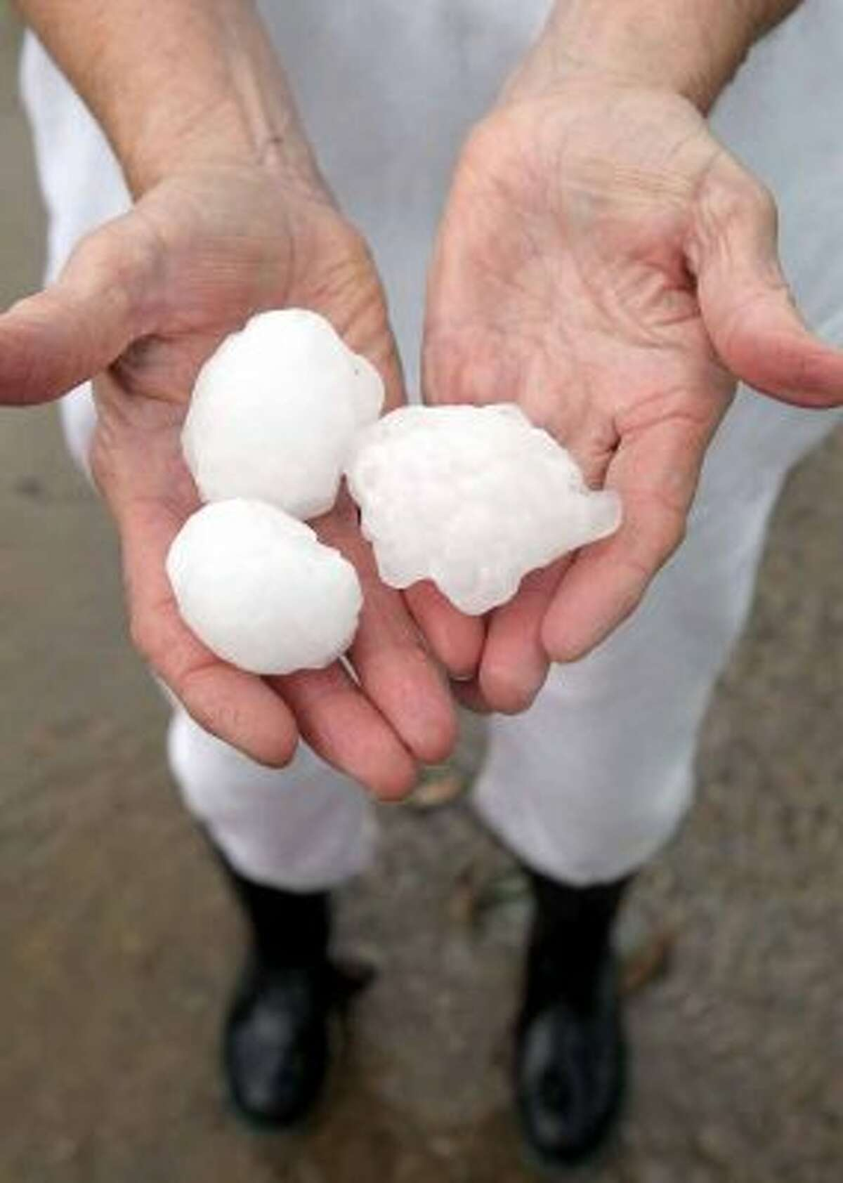 Melba Baker holds some of the golf ball plus size hail that fell at her home in Cunningham, Texas, Tuesday, April 3, 2012. Two large super cell thunderstorms brought heavy rain and damaging winds to North East Texas as well as tornadoes in the Dallas and Fort Woth area. (AP Photo/The Paris News, Sam Craft) (Associated Press)