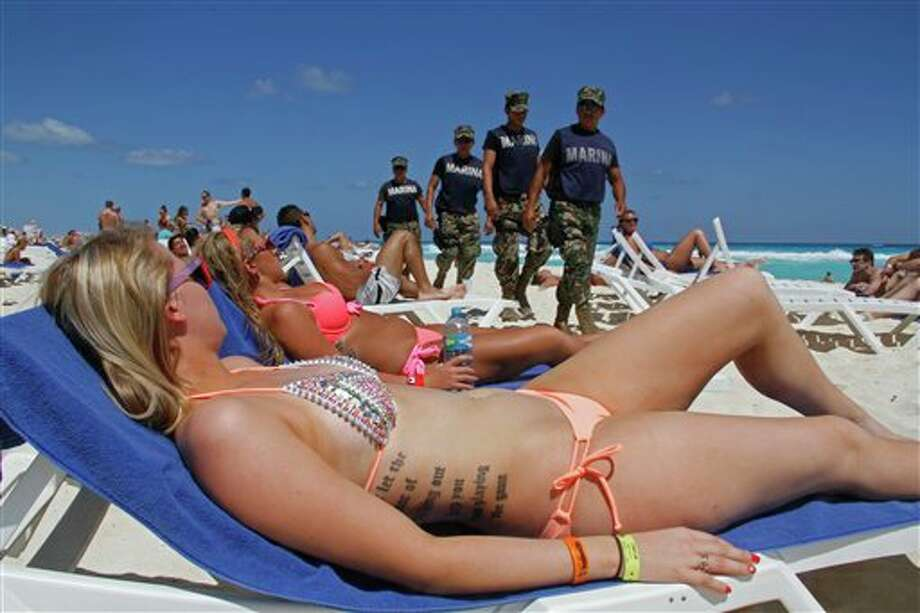 FILE - In this March 15, 2012 file photo, navy sailors patrol as people sun bathe on the beach during spring break in Cancun, Mexico. While American tourism to Mexico slipped a few percentage points last year, the country remains by far the biggest tourist destination for Americans, according to annual survey of bookings by the largest travel agencies. (AP Photo/Israel Leal, File) (AP)