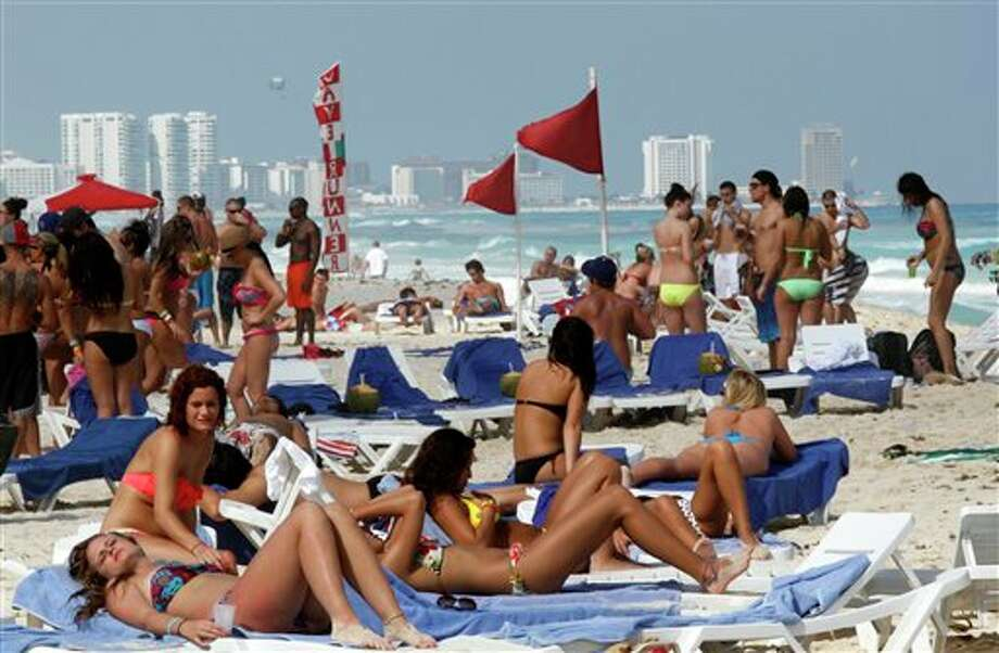 In this March 10, 2012 photo, people hang out on the beach during spring break in Cancun, Mexico. While American tourism to Mexico slipped a few percentage points last year, the country remains by far the biggest tourist destination for Americans, according to annual survey of bookings by the largest travel agencies. (AP Photo/Israel Leal) (AP)