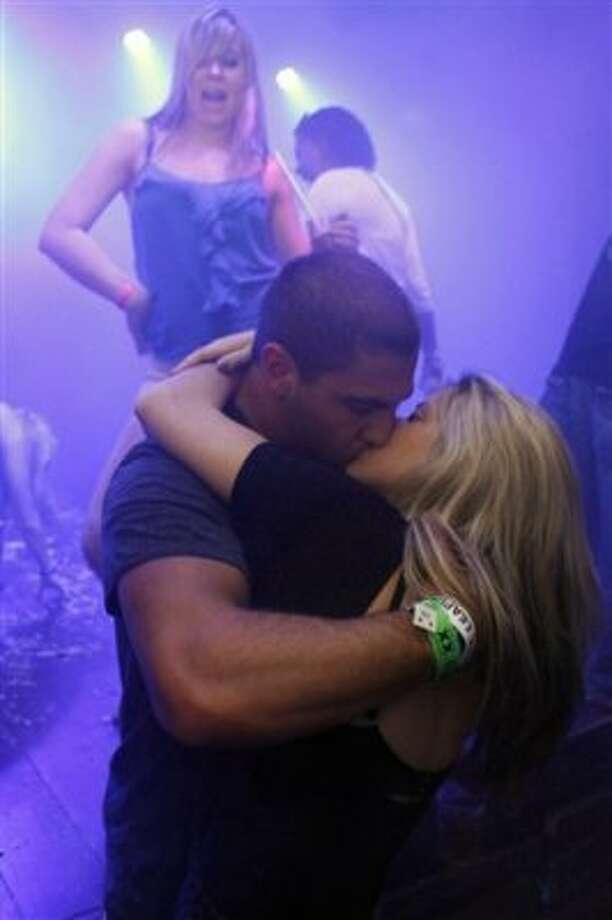 In this March 7, 2012 photo, people kiss at a bar during Spring Break in Cancun, Mexico. While American tourism to Mexico slipped a few percentage points last year, the country remains by far the biggest tourist destination for Americans, according to annual survey of bookings by the largest travel agencies. (AP Photo/Israel Leal) (AP)