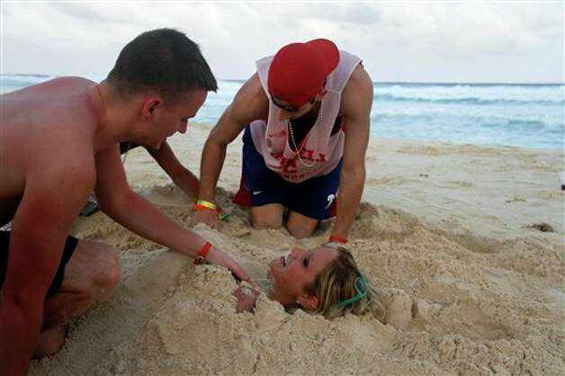In this March 7, 2012 photo, people bury eachother in the sand on the beach during Spring Break in Cancun, Mexico. While American tourism to Mexico slipped a few percentage points last year, the country remains by far the biggest tourist destination for Americans, according to annual survey of bookings by the largest travel agencies. (AP Photo/Israel Leal) (AP)