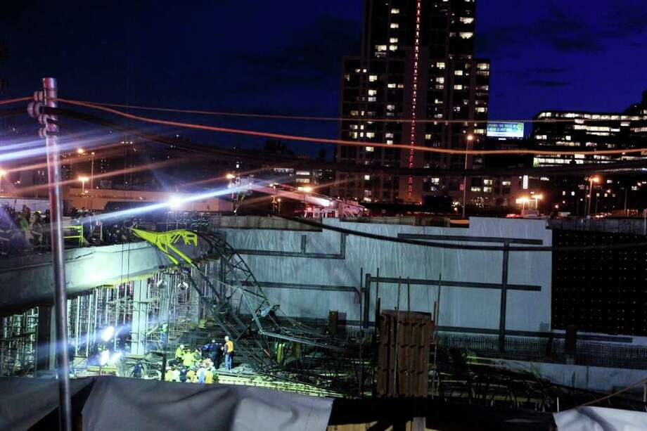 Emergency personel remove an injured man from the site of a crane collapse where construction is going on for the 7 line subway extension Tuesday, April 3, 2012, in New York. Fire officials say a crane collapse at a Manhattan construction site has injured two people. Photo: Frank Franklin II, AP / AP