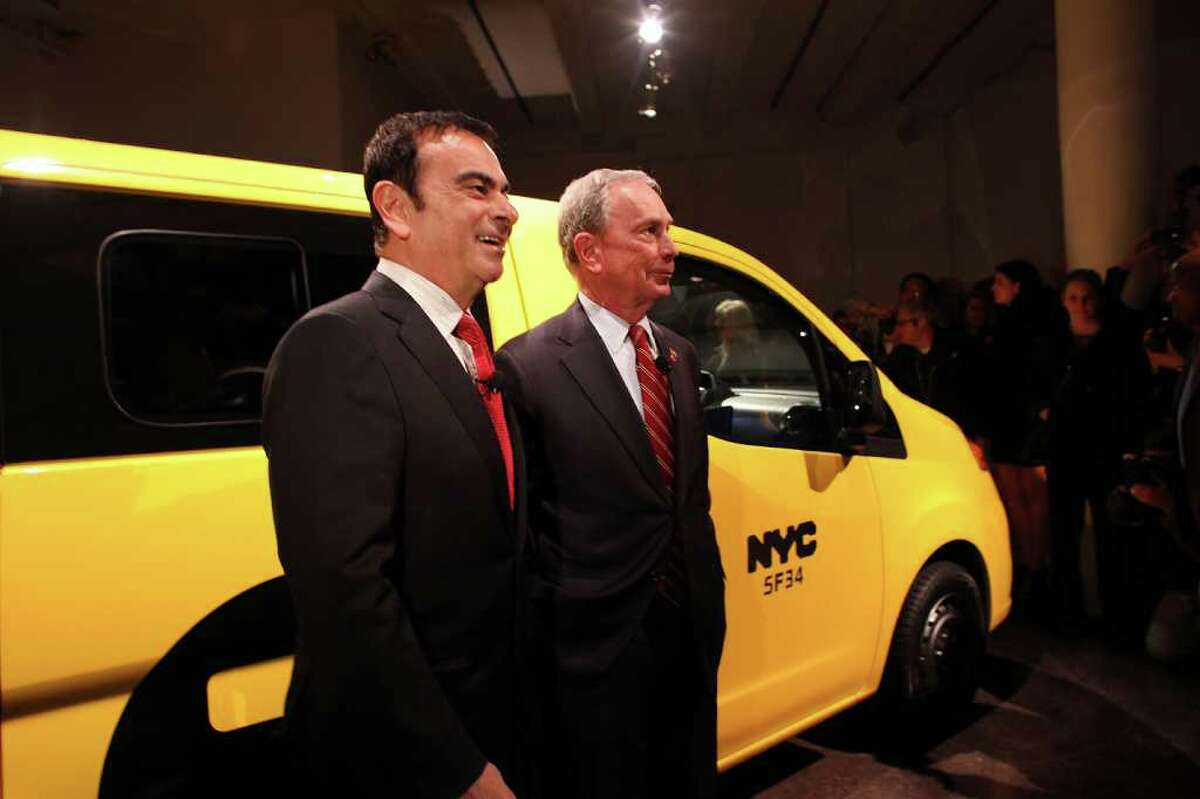 NEW YORK, NY - APRIL 03: New York Mayor Michael Bloomberg (right) and Nissan President and CEO Carlos Ghosn stand near the new New York City taxi which is designed by the Nissan Motor Co. at an official unveiling on April 3, 2012 in New York City. The new taxis, which will start appearing on the streets of New York next year, service an estimated service 600,000 people daily. The 2014 NV200 Taxi will replace the fleet of iconic Ford Crown Victorias, Ford Escape Hybrids and Toyota Siennas that are currently being used. Some of the highlights of the new taxi include front and rear-seat occupant curtain airbags, a window on the roof, backseat cellphone charging and USB ports and passenger reading lights.