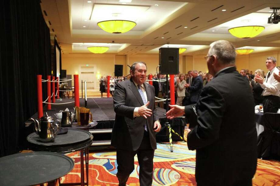 Gov. Mike Huckabee reaches to shake hands with PACN banquet emcee Carl Etchison following his speech.