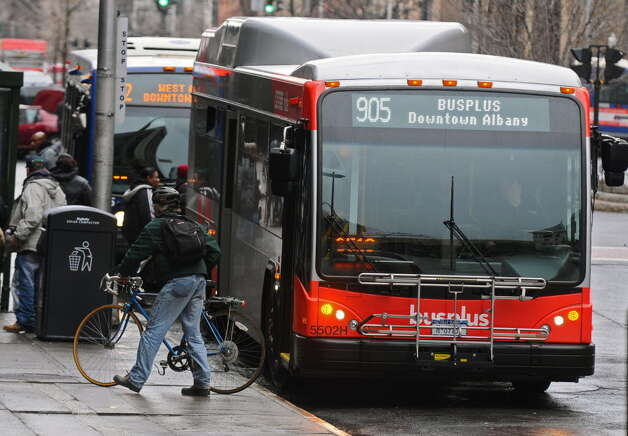 A rider takes his bike from the rack of the front of a bus after getting off one of the new BusPlus vehicles at South Pearl Street and State Street on Monday April 4, 2011 in Albany, NY. (Philip Kamrass/ Times Union )