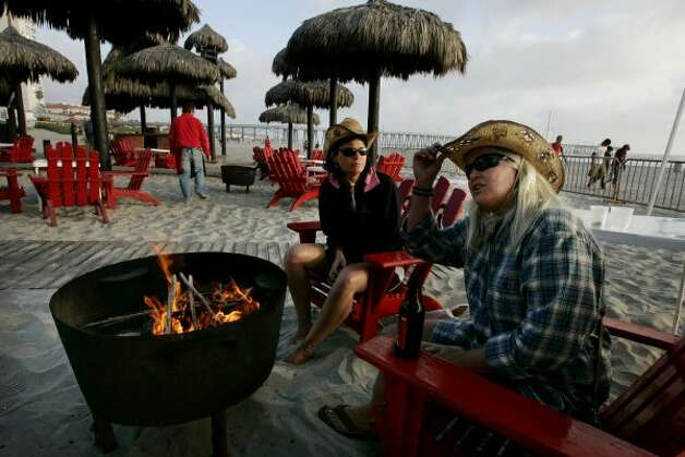 ROSARITO, MEXICO - APRIL 1: Carol Arthur (R) and Tammy Delu, from Seattle, sit at a bar along the beach April 1, 2009 in Rosarito, Mexico.  The tourist industry in some northern Mexican resort towns is feeling the effects of the ongoing drug war, as students from the U.S. are curtailing their spring break plans and traveling domestically instead.  (Photo by Sandy Huffaker/Getty Images) (Sandy Huffaker / Getty Images)