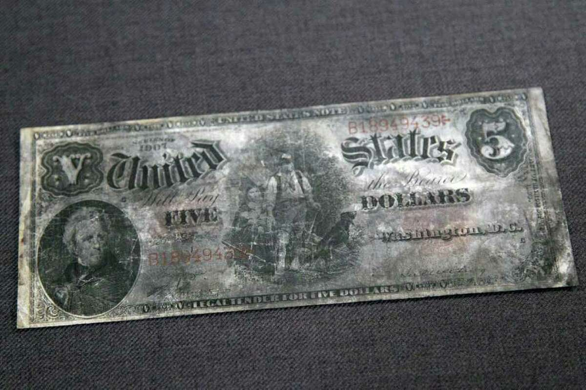 A five dollar bank note, series 1907, from the RMS Titanic Inc. is on display at Guernsey's Auctioneers & Brokers, Wednesday, April 4, 2012 in New York. The auction of more than 5,000 Titanic artifacts a century after the luxury liner's sinking has stirred hundreds of interested calls, with some offering to add to the dazzling trove already plucked from the ocean floor.