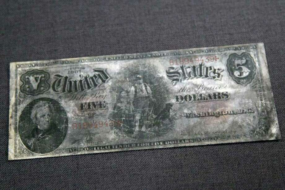 A five dollar bank note, series 1907, from the RMS Titanic Inc. is on display at Guernsey's Auctioneers & Brokers,  Wednesday, April 4, 2012 in New York.    The auction of more than 5,000 Titanic artifacts a century after the luxury liner's sinking has stirred hundreds of interested calls, with some offering to add to the dazzling trove already plucked from the ocean floor. Photo: Mary Altaffer, AP / AP