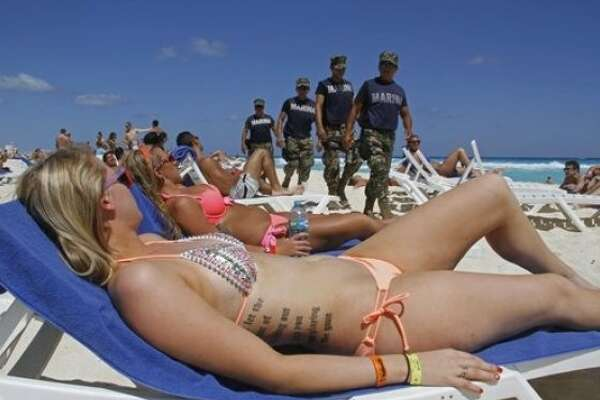 In this March 15, 2012 photo, navy sailors patrol as people sun bathe on the beach during spring break in Cancun, Mexico.