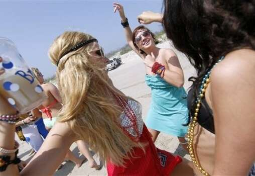 From left, Brooke Bryant, Ashton Ermis and Olivia Grace, all students from Texas Tech University, dance together Tuesday, March 13, 2012 on the beach in Port Aransas, Texas. Photo: Michael Zamora, AP, Corpus Christi Caller-Times