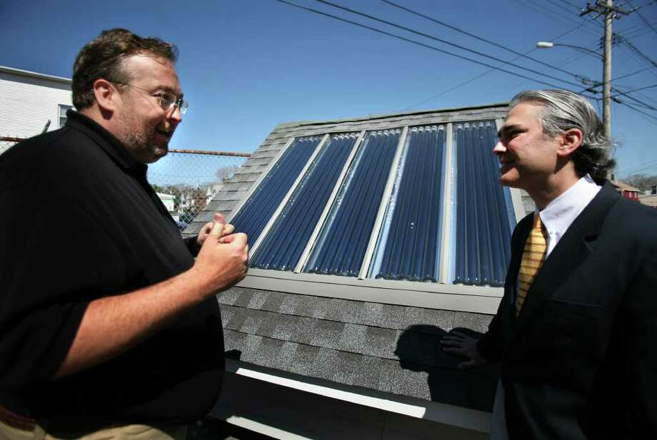 Scott Hartzell, left, president of SolarChange, shows State Senator Anthony Musto his company's solar heating product at the company facility at 277 Lenox Avenue in Bridgeport on Wednesday, March 4, 2012. Water is heated in tubes, which can then used for heating in baseboards and radiators, swimming pools, and domestic hot water. Photo: Brian A. Pounds / Connecticut Post