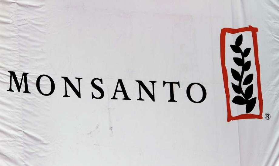 FILE - This Aug. 31, 2011 photo, shows the Monsanto corporate logo at their exhibit booth during the Farm Progress Show, in Decatur, Ill.   Monsanto Co. said Wednesday, April 4, 2012  that a strong and early U.S. seed selling season drove its fiscal second quarter net income up 19 percent. The U.S. agricultural giant also raised its earnings outlook for the full year. (AP Photo/Seth Perlman) Photo: Seth Perlman