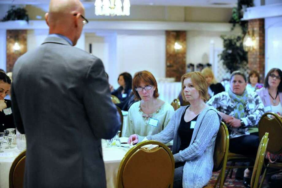 Arlen Bussell, center, and Jennifer Spagnolo, both of Brookfield, two parents who attended a workshop on drugs and mental health issues in high schools, listen to psychologist Charles Manos speak Wednesday, April 4, 2012. Manos is the special education director for Brookfield. Photo: Carol Kaliff / The News-Times