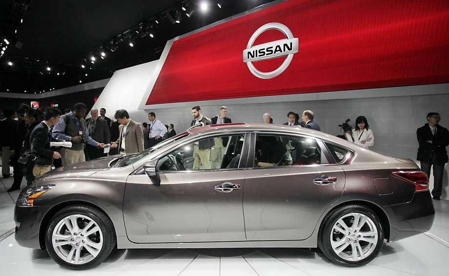 A crowd gathers around a 2013 Nissan Altima 3.5 SL sedan, Wednesday, April 4, 2012 at the New York International Auto Show. (AP Photo/Mark Lennihan) Photo: Mark Lennihan, Associated Press
