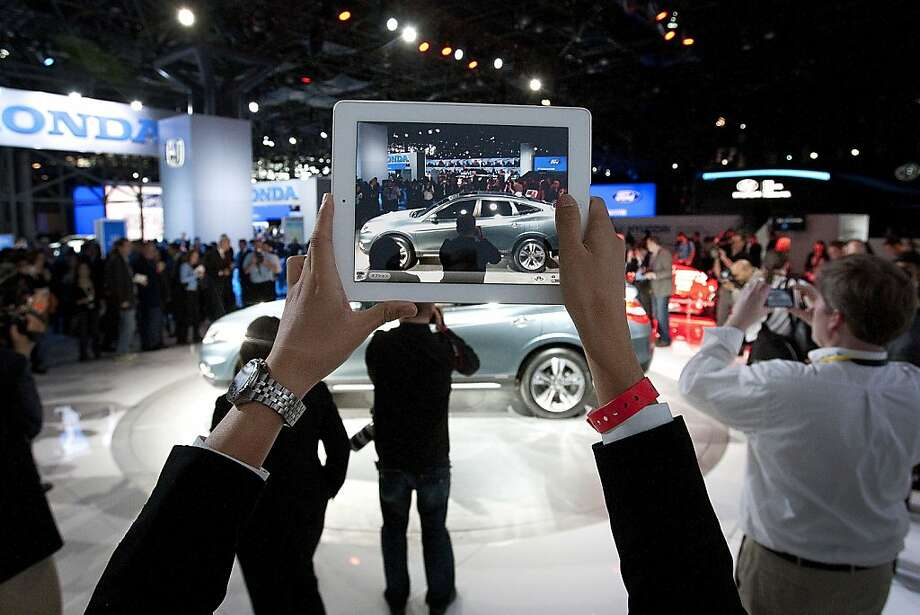 An attendee uses an Apple Inc. iPad to take a photo of the Honda Motor Co. Crosstour during a news conference at the New York International Auto Show in New York, U.S., on Wednesday, April 4th, 2012. The 2012 New York Auto Show is open to the public April 6-15. Photographer: Scott Eells/Bloomberg Photo: Scott Eells, Bloomberg