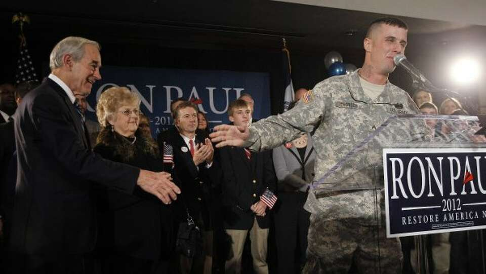 In this Jan. 3, 2012 photo, Republican presidential candidate Rep. Ron Paul, R-Texas, left, listens
