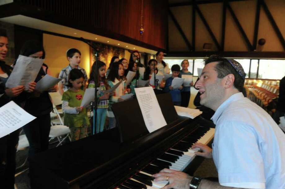 Jonathan Cahr leads the youth choir practice as they prepare for the Holocaust Remembrance Day Commemoration at Temple Sinai in Stamford, Conn., April 2, 2012.  The concert is open to the public and will take place on Thursday April 19th at 7 P.M. featuring Anita Schorr, a child Holocaust survivor, as the guest speaker. Photo: Keelin Daly / Stamford Advocate