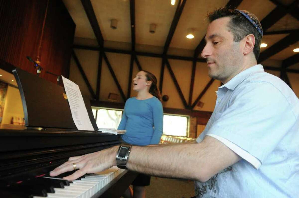 Fkanked by his daughter Alexandra Cahr, Jonathan Cahr leads the youth choir practice as they prepare for the Holocaust Remembrance Day Commemoration at Temple Sinai in Stamford, Conn., April 2, 2012. The concert is open to the public and will take place on Thursday April 19th at 7 P.M. featuring Anita Schorr, a child Holocaust survivor, as the guest speaker.