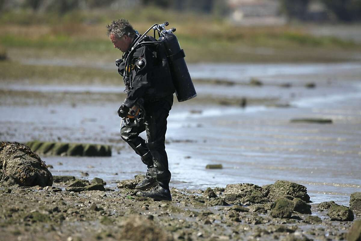 Without success divers with the Alameda County Sheriffs Department continue searching the estuary off of Martin Luther King Jr. Regional Shoreline, Wednesday April 4, 2012, for the weapon used in the killing of seven people at the Oikos University on Monday, in Oakland, Calif.