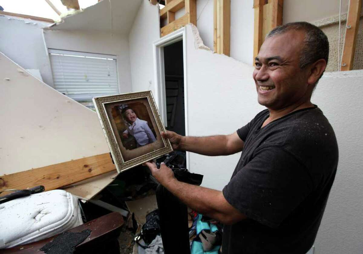 Juan Ventura Sr., smiles after discovering the portrait of his two-year-old grandson Adrian Ventura in the tornado damaged home of Ventura's son Wednesday, April 4, 2012, in Forney, Texas.