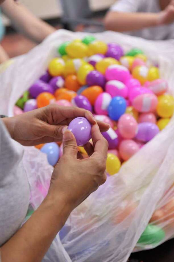 Members of the Hope Community Church stuff over 400 plastic eggs that will be used in a helicopter Easter egg drop at the church. Photo: Robin Jerstad, Robin Jerstad/For The Express-News