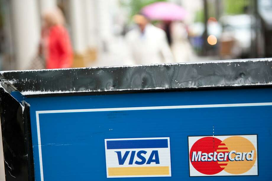 Visa and MasterCard credit card logos are seen on a sign in Washington on March 30, 2012. Credit card giants Visa and MasterCard were scrambling to thwart cyber crooks who looted a massive trove of precious account data, evidently from a payment processor in New York. Gartner analyst Avivah Litan said that industry sources revealed that numbers from more than 10 million credit card accounts were stolen in the breach, with the entry point being a New York City taxi and parking garage company.    AFP PHOTO/Nicholas KAMM (Photo credit should read NICHOLAS KAMM/AFP/Getty Images) Photo: Nicholas Kamm, AFP/Getty Images