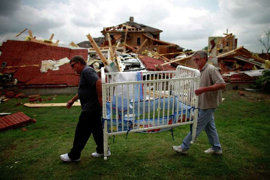 Mike Enochs (L) and Gary Enochs (R) salvage a baby crib from Mike Enochs' destroyed home after a tornado on April 4, 2012 in Forney, Texas. Multiple tornadoes touched down yesterday across the Dallas/Fort Worth area causing extensive damage. Photo: Tom Pennington, Getty Images / 2012 Getty Images