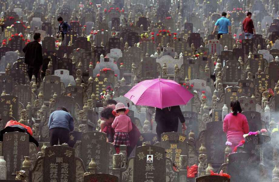 "Chinese families gather during the annual ""Qingming"" festival or Tomb Sweeping Day at a cemetary in Jinjiang, southeast China's Fujian province. During ""Qingming"" Chinese traditionally tend the graves of their departed loved ones and often burn paper money, model houses, cars, mobile phones and other goods as offerings to honour them and keep them comfortable in the afterlife. Photo: AFP, AFP/Getty Images / AFP"