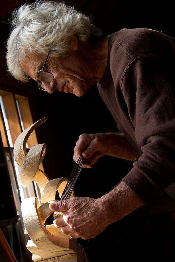 John McAbery, guided by experience and a window of natural light, works on a carving in his one-room cabin near Petrolia, Calif. Photo: Terrence McNally, Arcata Studios