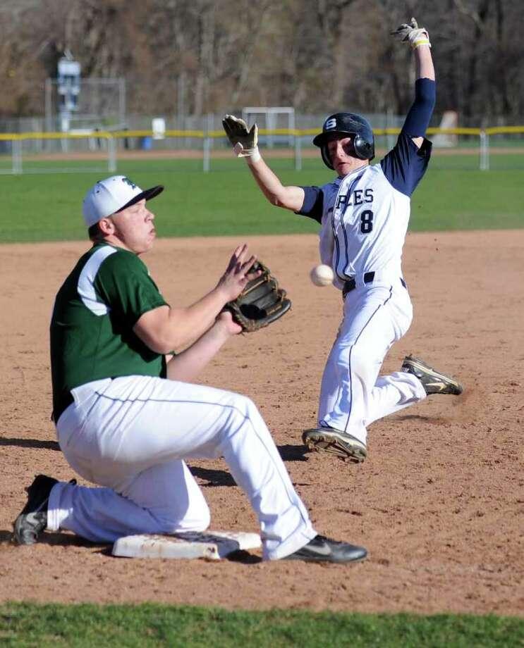 Staples' Matt Reynolds steals third base as Norwalk's Tyler Burns catches the ball Wednesday, April 4, 2012 during the baseball season opener at Staples High School. Photo: Autumn Driscoll / Connecticut Post