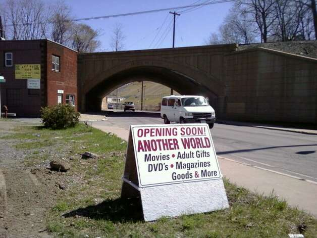 A sign advertises the opening of Another World adult bookstore on Lower ...