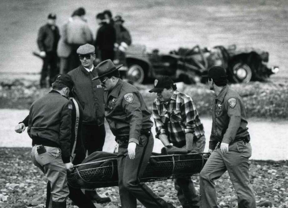 Rescue workers remove a body from the Schoharie Creek Thruway bridge site in Montgomery County, April 6, 1987. A Thruway bridge over the Schoharie Creek collapsed on April 5, 1987, after flood waters eroded its main supports. Ten motorists lost their lives. (Fred McKinney / Times Union archive)