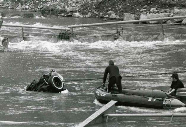 Police work to remove a car from the Schoharie Creek, April 12, 1987, following the April 5 Thruway bridge collapse which claimed the lives of ten motorists. (Fred McKinney / Times Union archive)