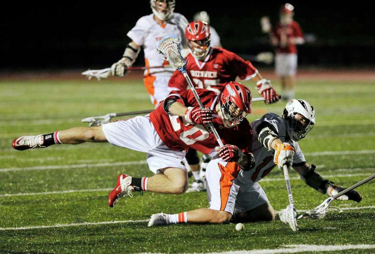 Greenwich's Shawn Dunster collides with Ridgefield's Eric Scala during their game at Ridgefield High School on Wednesday, April 4, 2012. Ridgefield won 11-4.