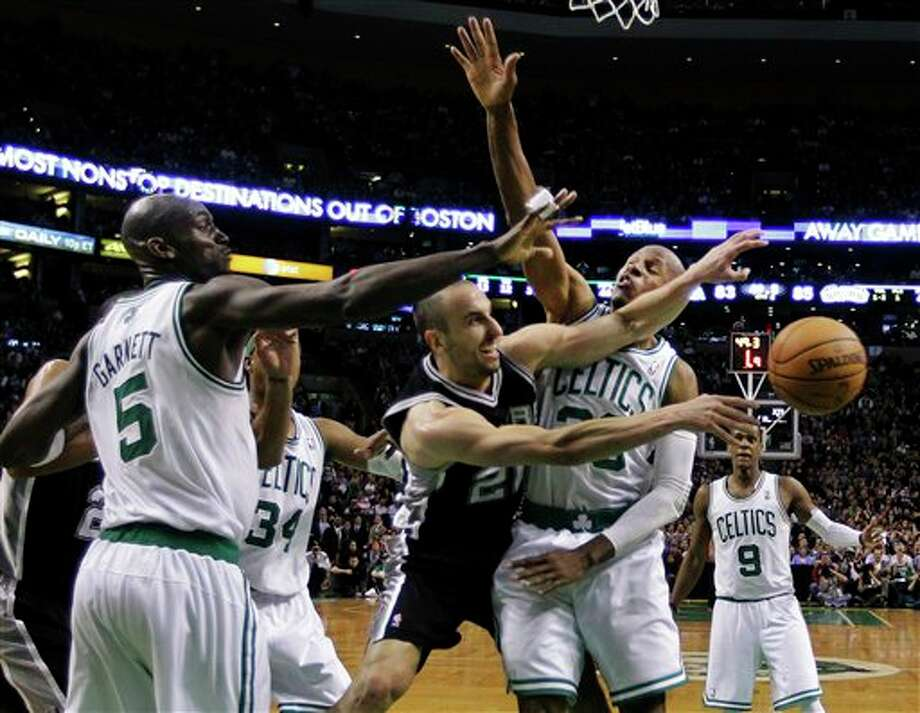 San Antonio Spurs guard Manu Ginobili (20) dishes the ball against Boston Celtics guard Ray Allen (20), forward Kevin Garnett (5) and forward Paul Pierce (34) in the second half of an NBA basketball game in Boston, Wednesday, April 4, 2012. The Spurs won 87-86. (AP Photo/Elise Amendola) (AP)