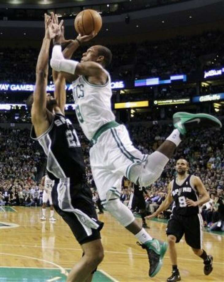 Boston Celtics guard Rajon Rondo (9) leans into a shot against San Antonio Spurs center Tim Duncan (21) as guard Tony Parker (9) watches during the first half of an NBA basketball game in Boston, Wednesday, April 4, 2012. (AP Photo/Elise Amendola) (AP)