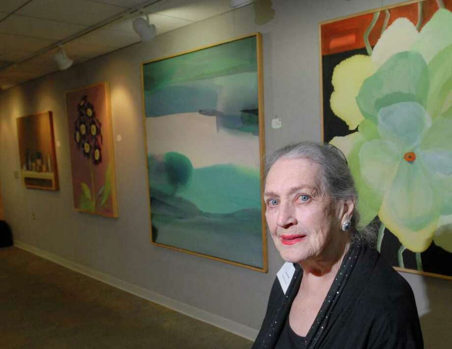 """Artist Janet Baldi of Greenwich stands near her paintings during a reception for her show, """"Freedom,"""" at the YWCA of Greenwich Wednesday night, April 4, 2012. Fifty percent of sales from the show will be donated to charitable organizations that look after homeless female veterans and their children, Baldi said. Photo: Bob Luckey / Greenwich Time"""