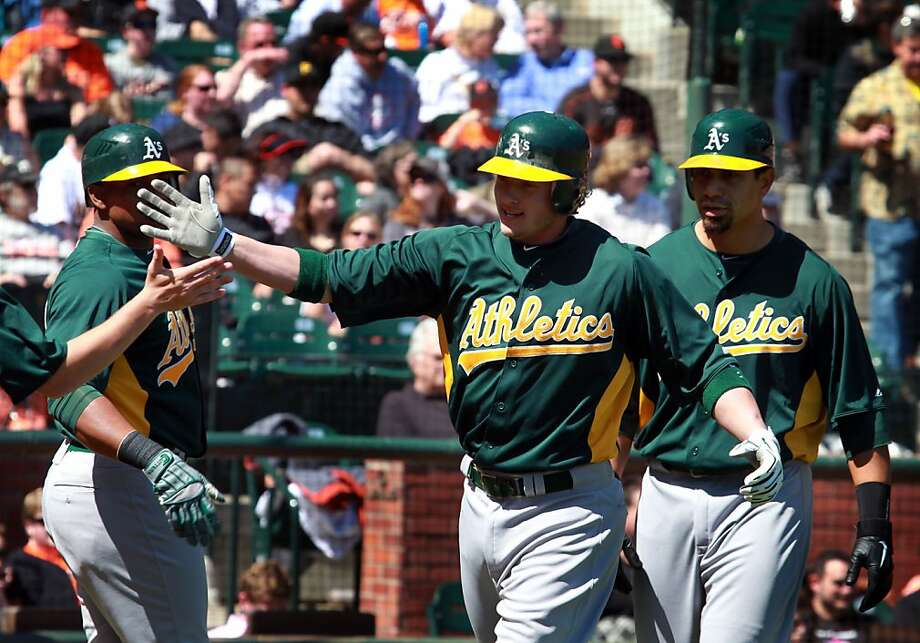 Oakland Athletics Josh Donaldson is greeted at the A's dugout after hitting a three-run home run against the San Francisco Giants in the fourth inning putting the A's on top 6-1 in their final spring training baseball game, in San Francisco Calif., on Wednesday, April 4, 2012. The A's won 8-1. Photo: Lance Iversen, The Chronicle