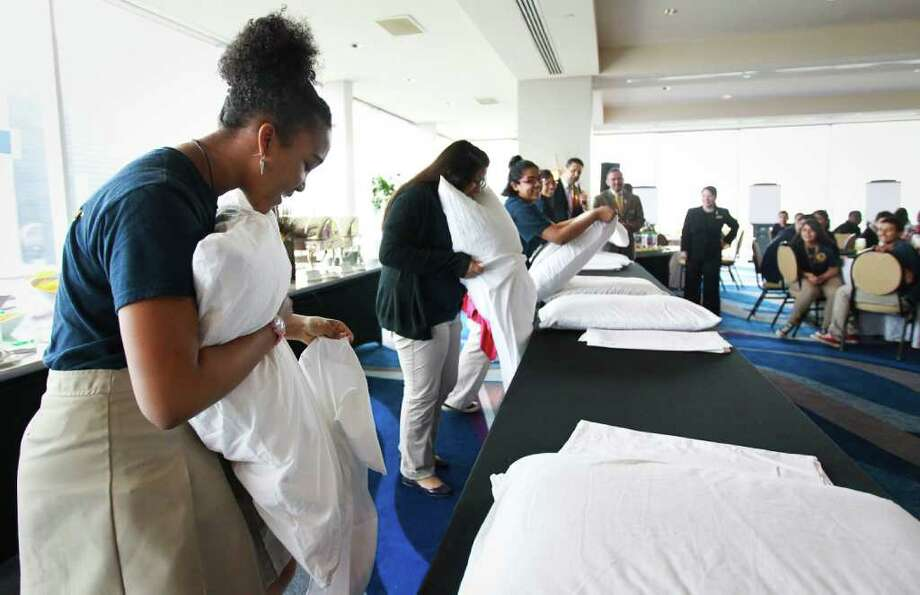 Tasiah Rodgers, a student from Marshall Middle School's Academy of Fine Arts, tries her hand at pillow-stuffing during a contest Wednesday at the Hilton Americas-Houston. Students went behind the scenes to learn how hotels operate. Photo: Nick De La Torre / © 2012  Houston Chronicle