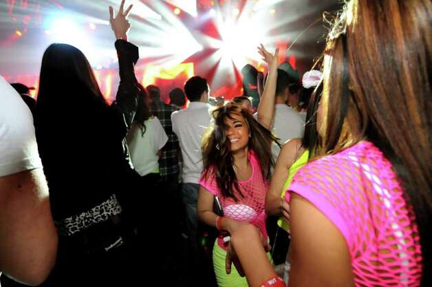 Juliet Cisala, 20, of Saratoga Springs, center, dances to the electronic music during the Winter White Tour on Thursday, Feb. 2, 2012, at the Washington Avenue Armory in Albany, N.Y. (Cindy Schultz / Times Union) Photo: Cindy Schultz /  00016306A