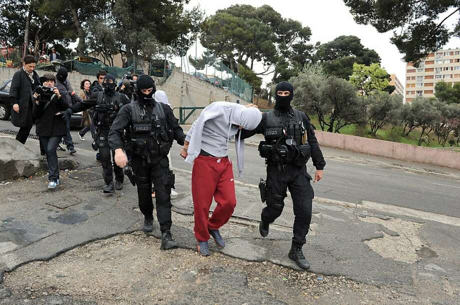 French members of the French National Police Intervention Group (GIPN) arrest a suspected radical Islamists group member, on April 4, 2012, in the French southern city of Marseille, as part of down raids in several French cities.  French police swooped on suspected radical Islamists in pre-dawn raids for the second time in less than a week today, arresting 10 people, a source close to the investigation said. Photo: Gerard Julien, AFP/Getty Images