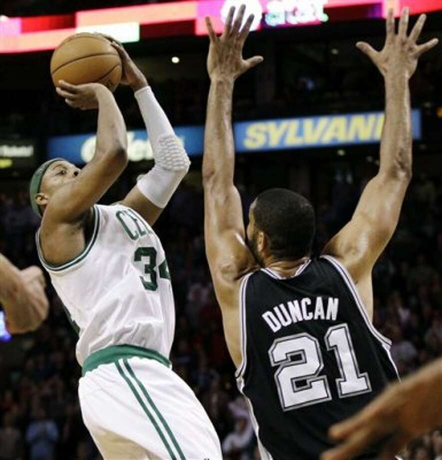 San Antonio Spurs center Tim Duncan (21) defends against a shot attempt by Boston Celtics forward Paul Pierce (34) in the last seconds of an NBA basketball game in Boston, Wednesday, April 4, 2012. The Spurs won 87-86. (AP Photo/Elise Amendola) (AP)