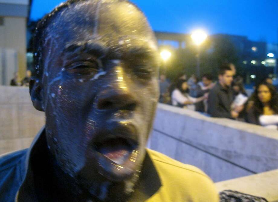 In this photo provided by David Steinman, Nnaemeka Alozie, campaign manager for Steinman, reacts with milk on his face after being sprayed with pepper spray during a protest on Tuesday, April 3, 2012, in Santa Monica, Calif. Campus police pepper-sprayed as many as 30 demonstrators after Santa Monica College students angry over a plan to offer high-priced courses tried to push their way into a trustees meeting Tuesday evening, authorities said. (AP Photo/Courtesy David Steinman) Photo:  David Steinman, Associated Press