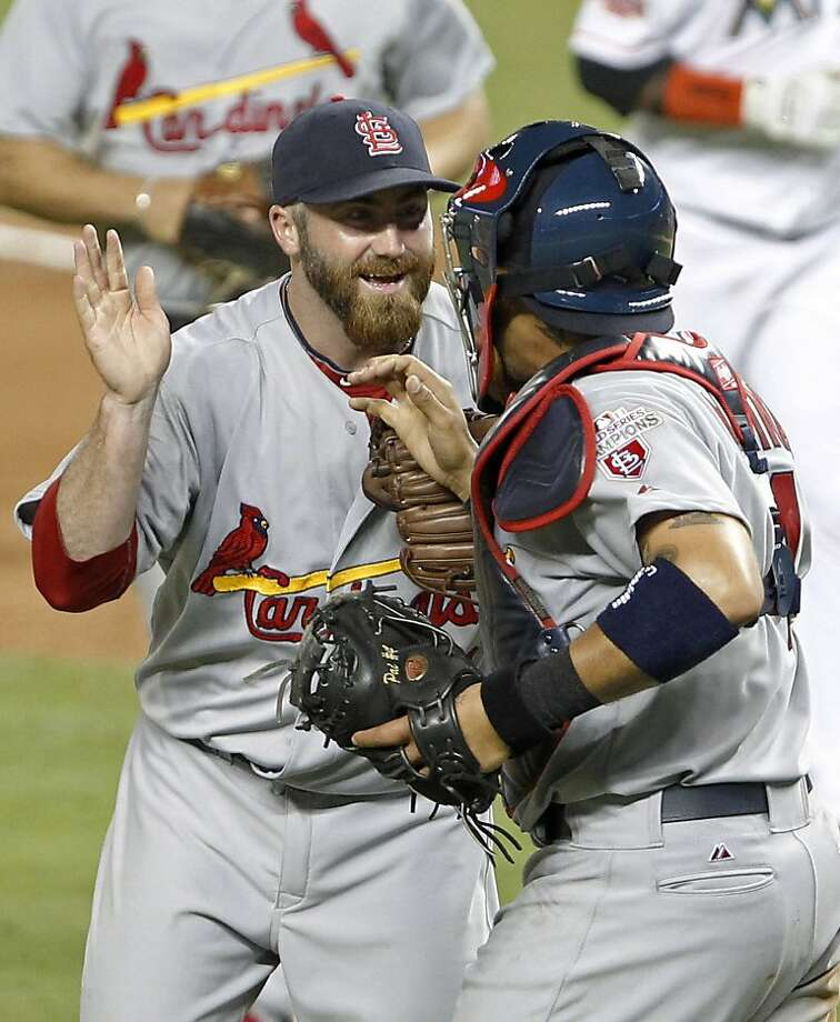 St. Louis Cardinals pitcher Jason Motte, left, celebrates with catcher Yadier Molina after the Cardinals defeated the Miami Marlins 4-1i n the Opening-Day baseball game, Wednesday, April 4, 2012, in Miami. (AP Photo/Wilfredo Lee) Photo: Wilfredo Lee, Associated Press